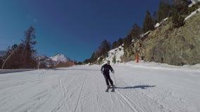 O esquiador rola para baixo a inclinação de cinzeladura do esqui do inverno nas montanhas filme