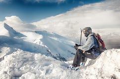 O esquiador senta-se com os esquis na rocha grande no contexto das montanhas Bansko, Bulgária fotos de stock royalty free