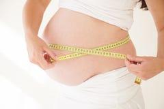 O estômago de uma mulher gravida e de uma fita de medição Imagens de Stock