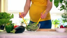 O estômago e as mãos fêmeas grávidos misturam a salada no prato de vidro na tabela video estoque