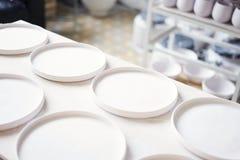 O estúdio cerâmico, argila branca plana chapeia pronto para vitrificar e o cozimento Fotografia de Stock