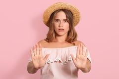 O estúdio disparado da fêmea nova desagradada com expressão do descontentamento, mulher atrativa mantém as palmas na frente da câ fotografia de stock