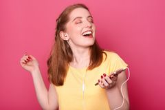 O est?dio disparado de rir a menina de cabelo vermelha nova com olhos fechados que escuta a m?sica, aprecia a melodia, guardando  imagem de stock royalty free