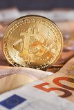 O estúdio disparou da moeda dourada física do bitcoin em 50 euro- cédulas das contas Bitcoin é uma moeda cripto do blockchain Mac Fotografia de Stock