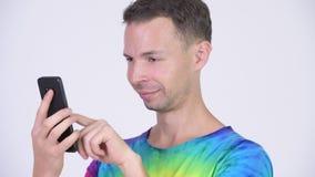 O estúdio disparou do homem feliz com camisa da laço-tintura usando o telefone video estoque