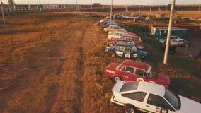 O estacionamento de um grande número carros preparou-se especialmente para a tração no estacionamento de uma estrada secundária vídeos de arquivo