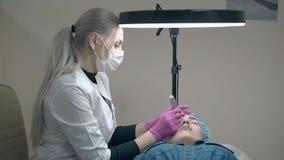 O esteticista aplica a composição da sobrancelha sob a lâmpada redonda preta vídeos de arquivo