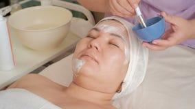 O esteticista aplica o creme branco da massagem com uma escova à cara de uma mulher de meia idade oriental Menina asiática em um  video estoque