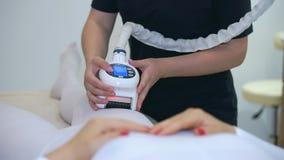 O esteticista da menina usa o equipamento cosmético moderno Terapia do laser do hardware vídeos de arquivo