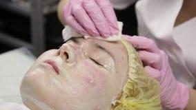 O esteticista do doutor remove a máscara de limpeza facial branca da cara do paciente vídeos de arquivo