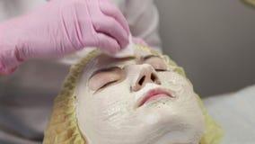 O esteticista do doutor remove a máscara de limpeza facial branca da cara do paciente filme