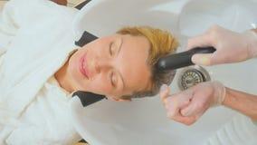O esteticista do homem lava o cabelo do cliente na clínica da beleza vídeos de arquivo