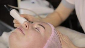 O esteticista faz o procedimento do levantamento de cara do rf para uma mulher em um bar da beleza Cosmetologia do hardware filme