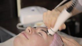 O esteticista faz o procedimento do levantamento de cara do rf para uma mulher em um bar da beleza Cosmetologia do hardware video estoque