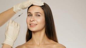 O esteticista faz uma anti-idade disparado com uma seringa na área da testa de um movimento lento da menina bonita filme