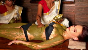 O esteticista indiano das mulheres aplicou a argila terapêutica de natural ao corpo do paciente