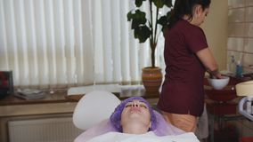 O esteticista limpa a cara do paciente fêmea com um botão do algodão antes do procedimento, desinfecção vídeos de arquivo