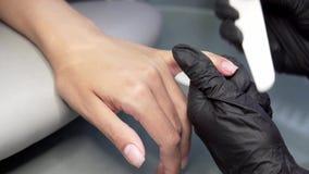 O esteticista mói a barra de prego para um tratamento de mãos no salão de beleza Tratamento do prego do dedo, moendo e lustrando vídeos de arquivo