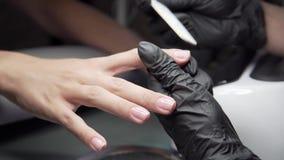 O esteticista mói a barra de prego para um tratamento de mãos no salão de beleza Tratamento do prego do dedo, moendo e lustrando video estoque