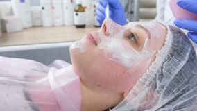 O esteticista põe uma máscara branca sobre a cara da mulher com uma escova Mãos de um cosmetologist em luvas de borracha azuis fa filme