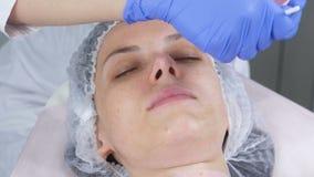 O esteticista põe uma máscara sobre a cara da mulher com uma escova Mãos de um cosmetologist em luvas de borracha azuis facial filme