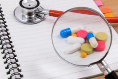 O estetoscópio, amplia e muitos comprimidos coloridos no bloco de notas vazio fotografia de stock royalty free