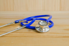 O estetoscópio de um doutor no fundo de madeira Fotografia de Stock Royalty Free