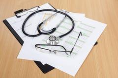 O estetoscópio e os monóculos sairam em uma prancheta dos trabalhadores médicos Foto de Stock