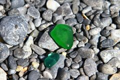 O estilhaço de vidro bonito lustrado pelo mar nas pedras escuras da praia - pedras pretas do seixo na praia Foto da natureza imagem de stock royalty free