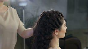 O estilista aplica a laca no penteado no salão de beleza video estoque