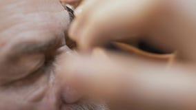 O estilista corta as testas do homem maduro com tesouras vídeos de arquivo
