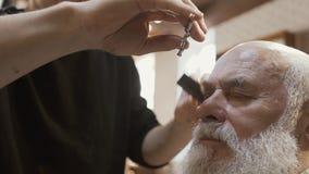 O estilista corta as testas do homem superior video estoque