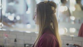 O estilista da mulher aplica a laca no penteado no salão de beleza video estoque