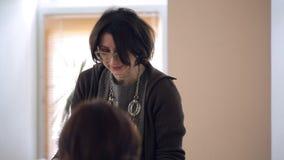 O estilista da mulher conduz o grupo que aconselha no tema do lenço de pescoço do uso video estoque
