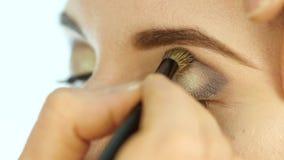 O estilista da mulher põe a sombra para os olhos escura sobre as pálpebras de uma noiva loura com uma escova especial Composição  filme