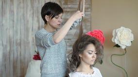 O estilista do maquilhador trabalha com modelo o cabeleireiro faz a denominação do cabelo do modelo o cabeleireiro cria um volume video estoque