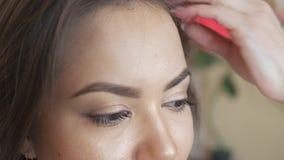 O estilista do maquilhador trabalha com modelo o cabeleireiro faz a denominação do cabelo do modelo E video estoque