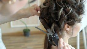 O estilista do maquilhador trabalha com modelo o cabeleireiro faz a denominação do cabelo do modelo a mulher está trabalhando um  filme