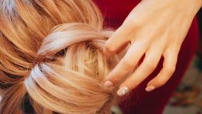 O estilista endireita o cabelo do braço de seu cliente A vista da parte superior Fim acima vídeos de arquivo
