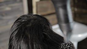 O estilista faz o cabelo que denomina para o cliente fêmea bonito e o secador de cabelo usado com pente filme