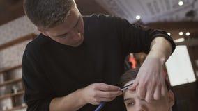 O estilista faz o contorno ao corte de cabelo com lâmina video estoque