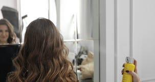 O estilista faz um penteado para o modelo moreno fêmea e aplica um pulverizador da fixação do cabelo video estoque
