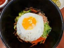O estilo coreano do alimento, vista superior do arroz é coberto com vegetais temperados, carne e lado acima do ovo frito na parte fotografia de stock