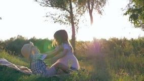 O estilo de vida feliz, crianças saudáveis tem o divertimento e o jogo junto no campo no por do sol filme