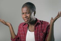O estilo de vida isolou o retrato da mulher americana nova do africano negro bonito e infeliz que gesticula com mãos e expressão  imagens de stock
