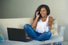 O estilo de vida isolou o retrato da mulher americana nova do africano negro feliz e lindo que fala no telefone celular ao trabal imagens de stock