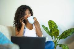 O estilo de vida isolou o retrato da mulher preta feliz e lindo nova do americano latino-americano que fala no telefone celular a imagens de stock