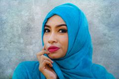 O estilo de vida isolou o retrato do sorriso asiático bonito e feliz novo da mulher coberto pelo lenço muçulmano da cabeça do hij foto de stock royalty free