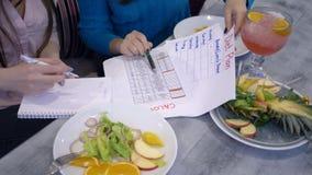O estilo de vida saudável, meninas faz calorias da contagem com o calendário do planeamento da dieta na folha de papel durante o  vídeos de arquivo