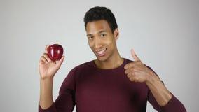 O estilo de vida saudável, o homem que mostram Apple vermelho e os polegares levantam o gesto vídeos de arquivo